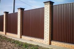 Забор из коричневого профнастила с кирпичными столбами